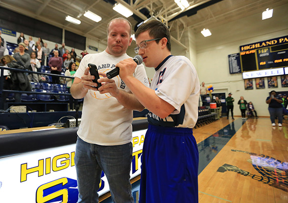 Highland Park ISD Special Olympics Coordinator Tyson Peterson helps a player recite the Special Olympics oath