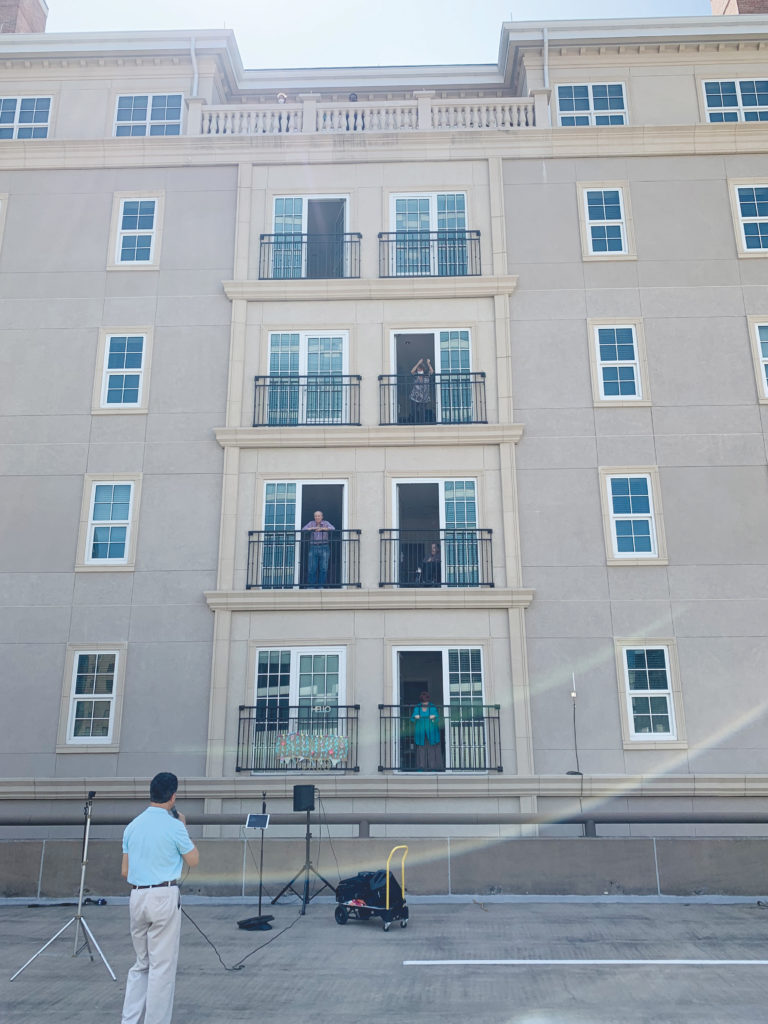 Preston of the Park Cities residents gather on balconies as singer Marty Ruiz serenades them from a parking structure below. (COURTESY PHOTO)