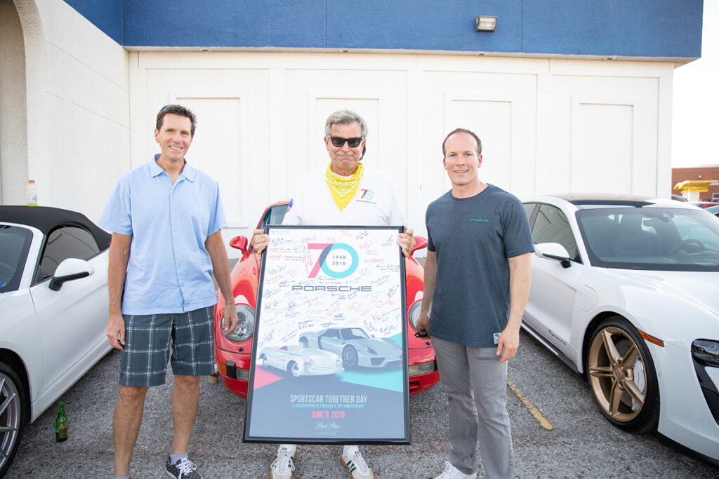 Porsche Cars North America Regional Manager Steve Krysil, Porsche Club of America – Maverick Region president Bill Kruder, and Park Place Porsche Dallas General Manager Patrick Huston at the June 8 celebration at Keller's Drive-In on Northwest Highway in Dallas. Kruder (center) is holding a framed posted signed by each of the 2018 attendees at the 70th Porsche anniversary at Park Place Porsche Dallas on Lemmon Ave.